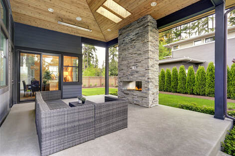 Exposed aggregate concrete back patio with furniture and grill